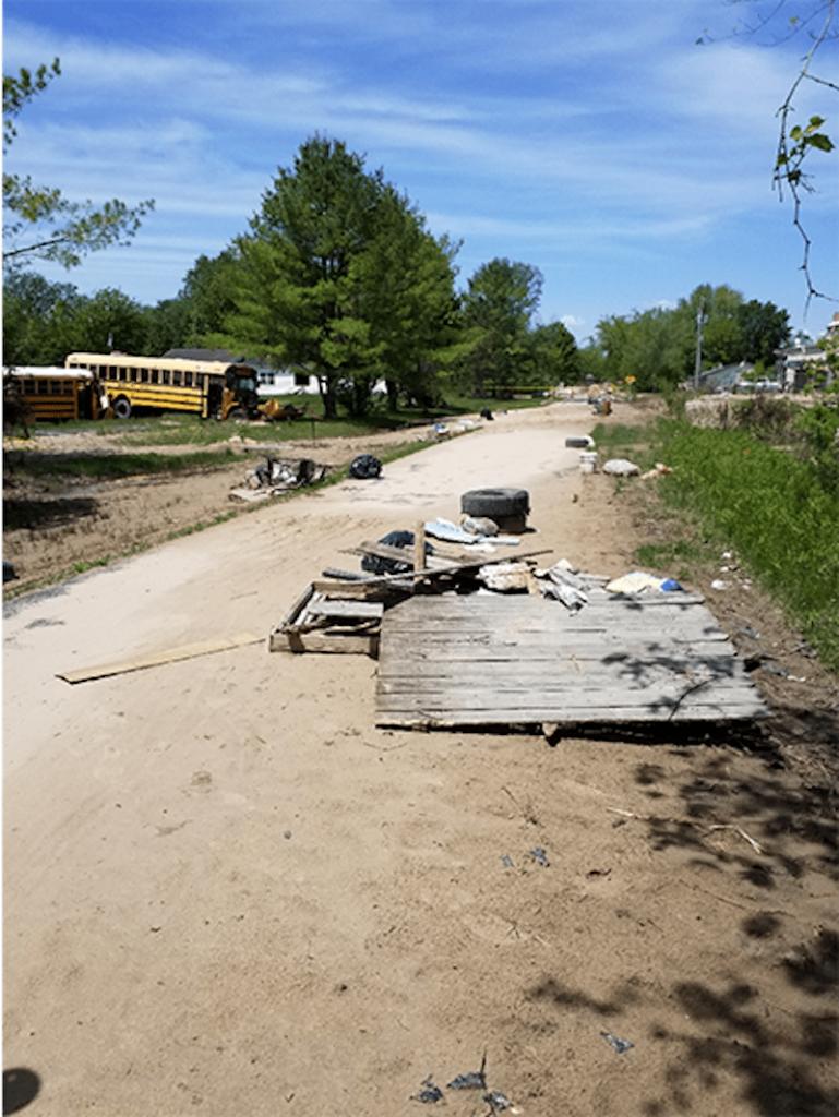 Flood debris is scattered across a road.