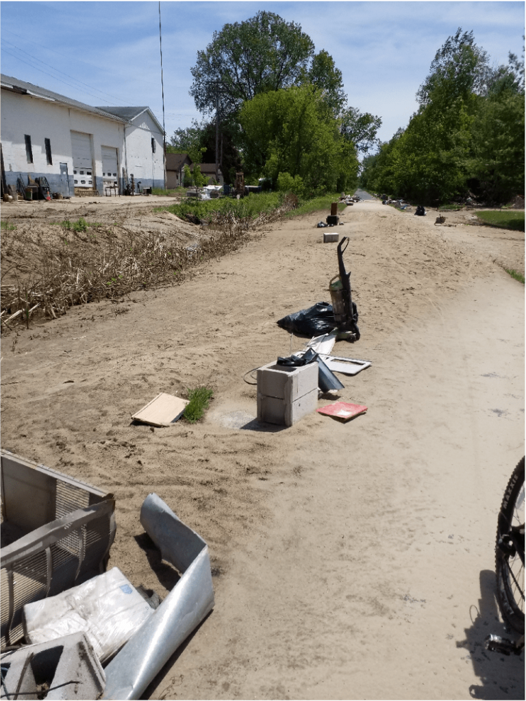 Vacuums and other debris are strewn across the trail from the flood.
