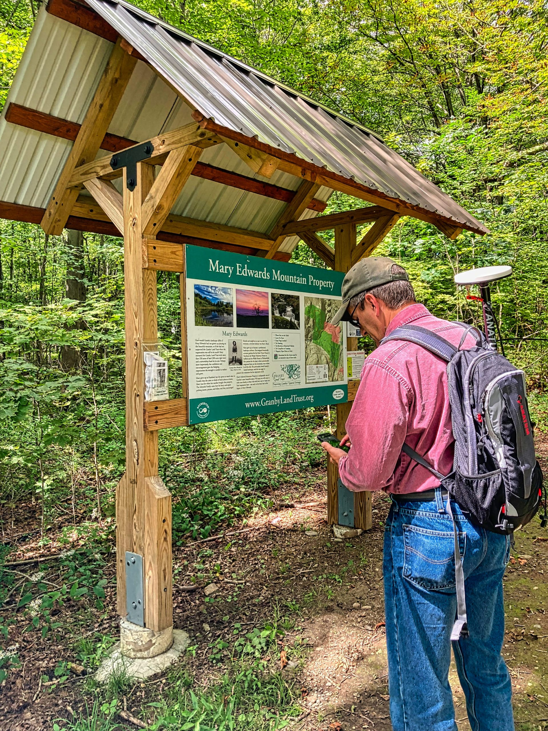 Steve Perry collects high accuracy GNSS GPS data in front of a trail, he is in the field for a land trust conservatorory using Esri ArcGIS Field Maps