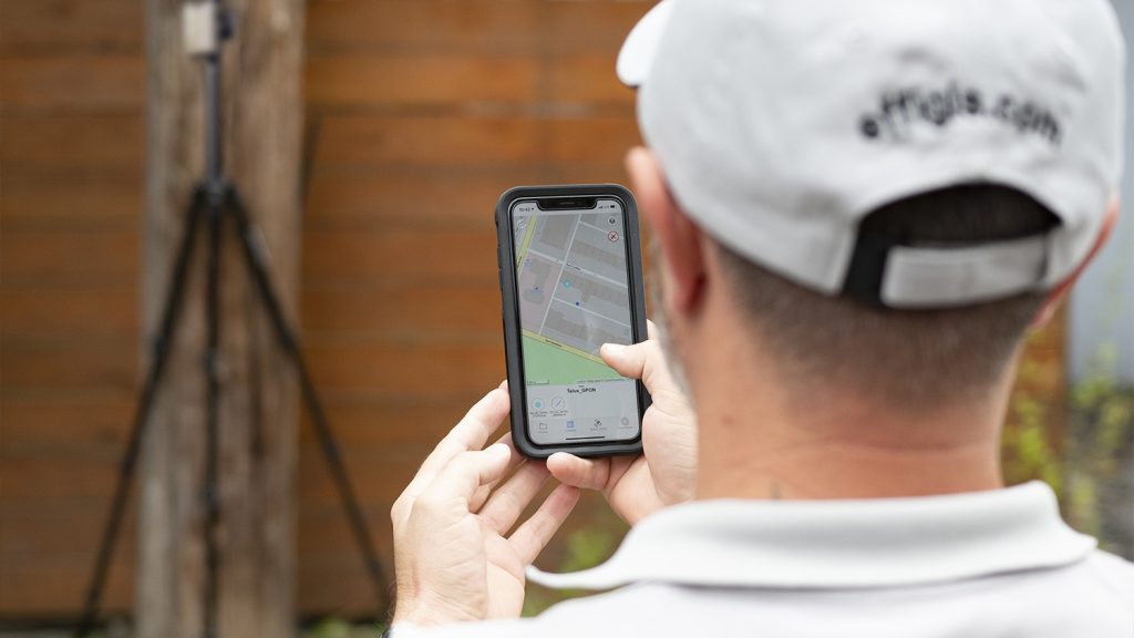 Mobile worker captures accurate GNSS positions in Esri partner app OnPOZ Collect from Effigis with Arrow Gold RTK GNSS receiver in the background